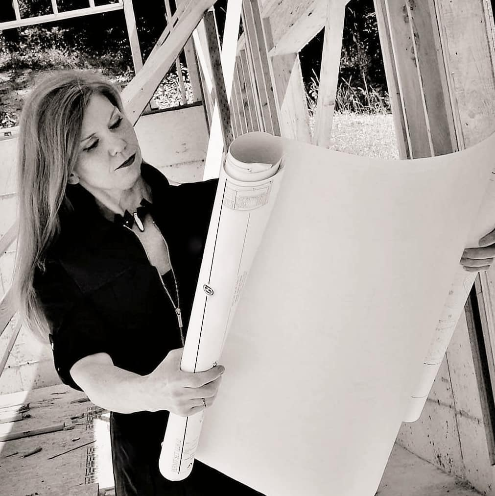 Founder of Dana Foster Interiors looking at blueprints