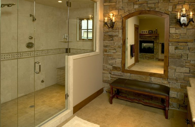 Walk-in shower and sitting bench with mirror, stone wall