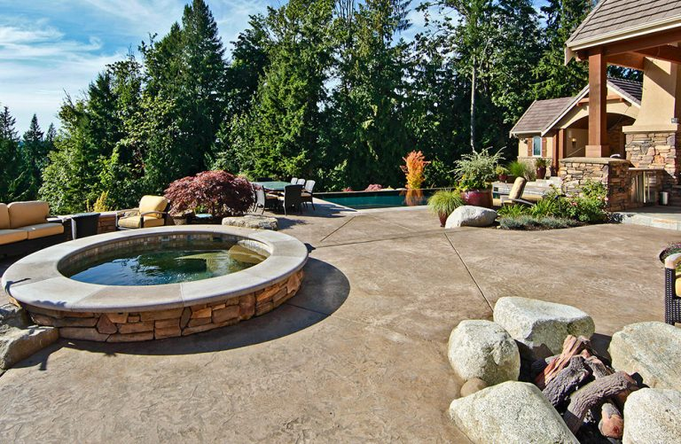 patio with hot tub and pool in the distance